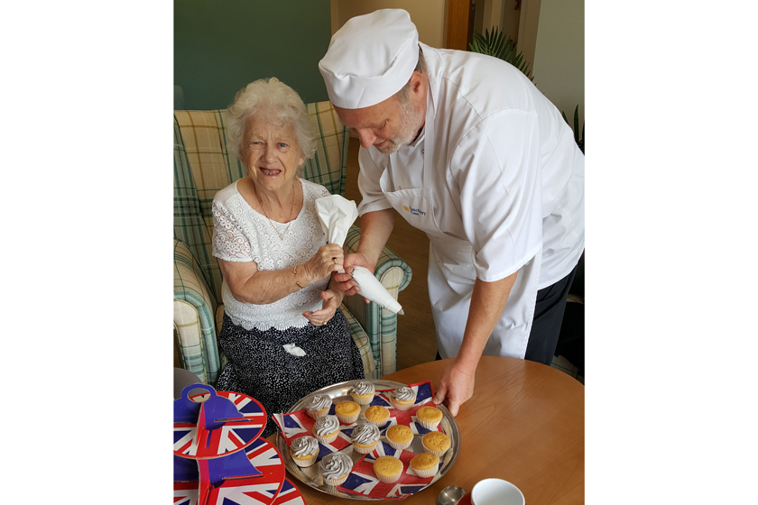 The Park View chef helping a resident to decorate cakes.
