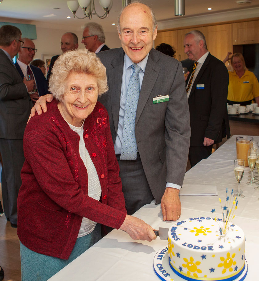 A Sanctuary Group board member and Briggs Lodge resident cutting the celebration cake.