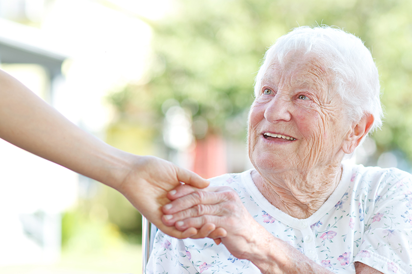 Elderly woman holding hands with caretaker