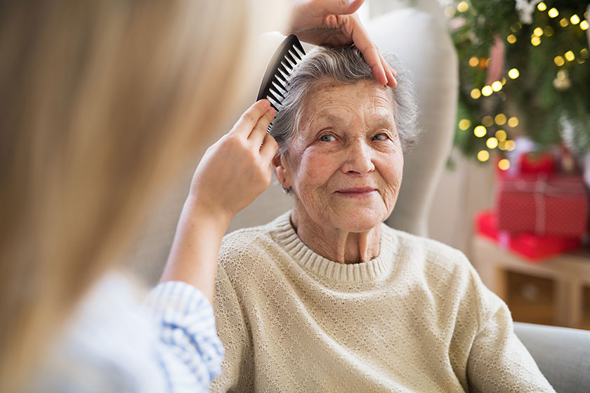An elderly care resident having her hair combed by a member of care staff