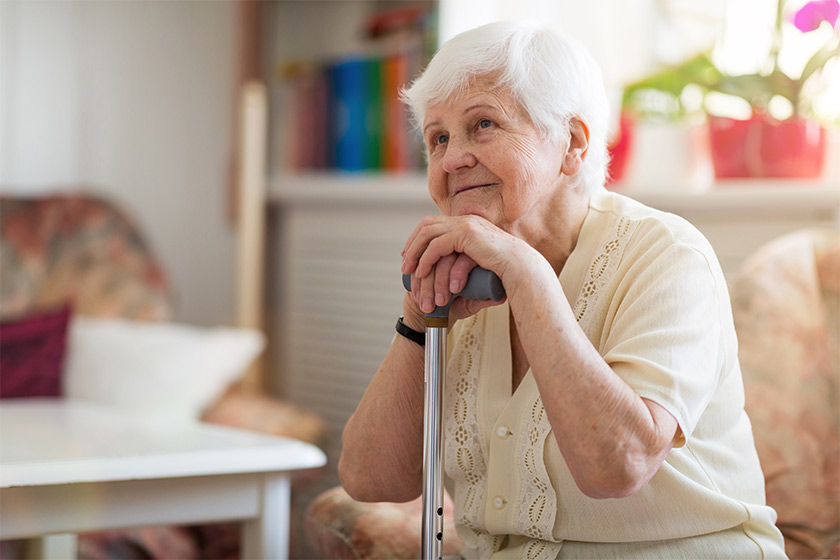 An elderly care resident smiling as she rests on her walking stick