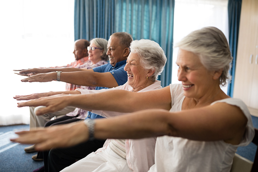 Elderly people doing exercise in a care home