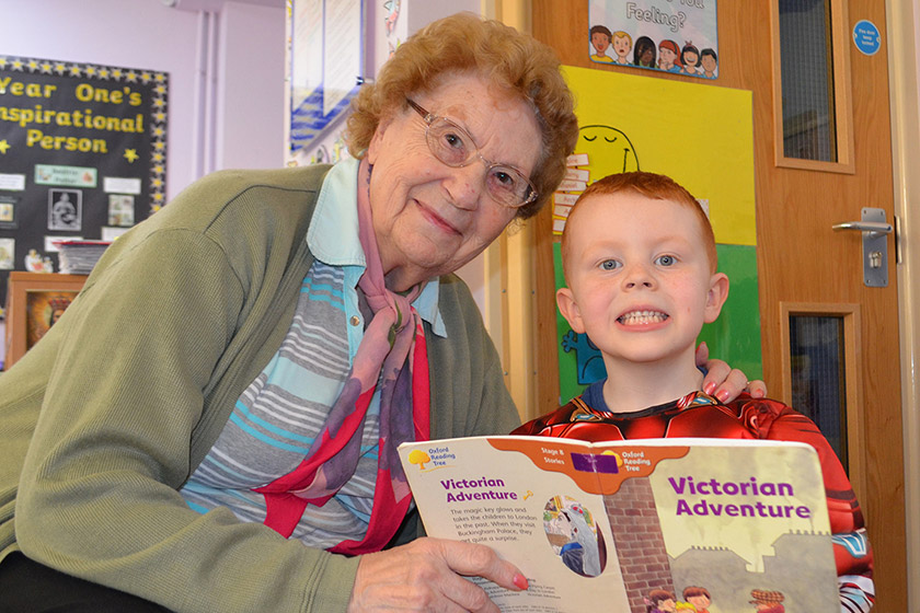 Care resident and a boy from a local school reading together
