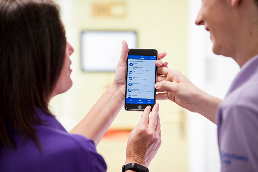 Two Sanctuary Care staff members holding a mobile phone with the kradle care app visible