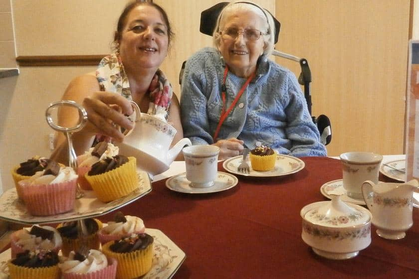 A staff member and resident enjoying tea and cakes.