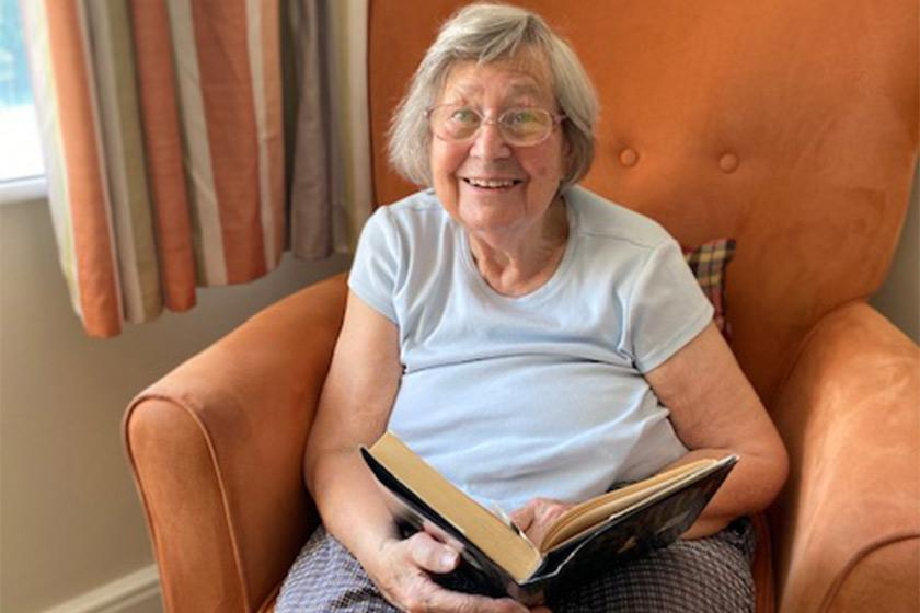 Sanctuary Care resident June Watson holding a book