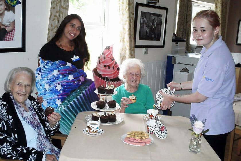 Residents, a volunteer and the Lime Tree care assistant with cupcakes and tea.