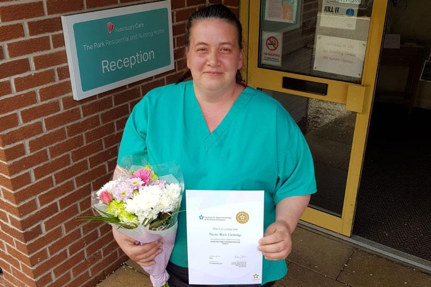 Nicola outside The Park Residential and Nursing Home, holding her foundation degree.