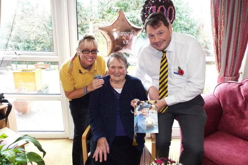 Margaret celebrating her 100th birthday with Sanctuary Care staff members.
