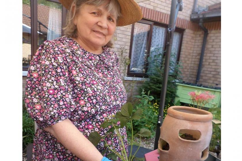 Caton House resident Jenny Rawlings wearing a summer outfit doing some gardening
