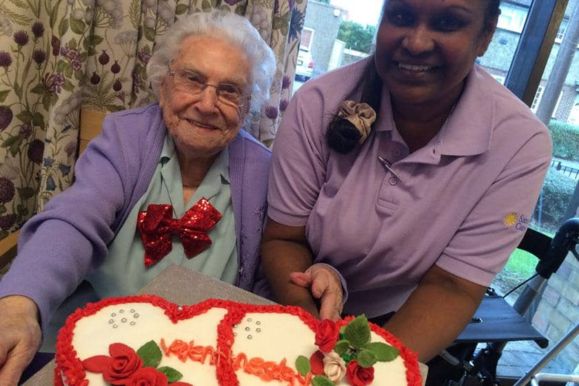 102-year-old resident Lucy Savage and staff member Udaya Manikkalatnam.