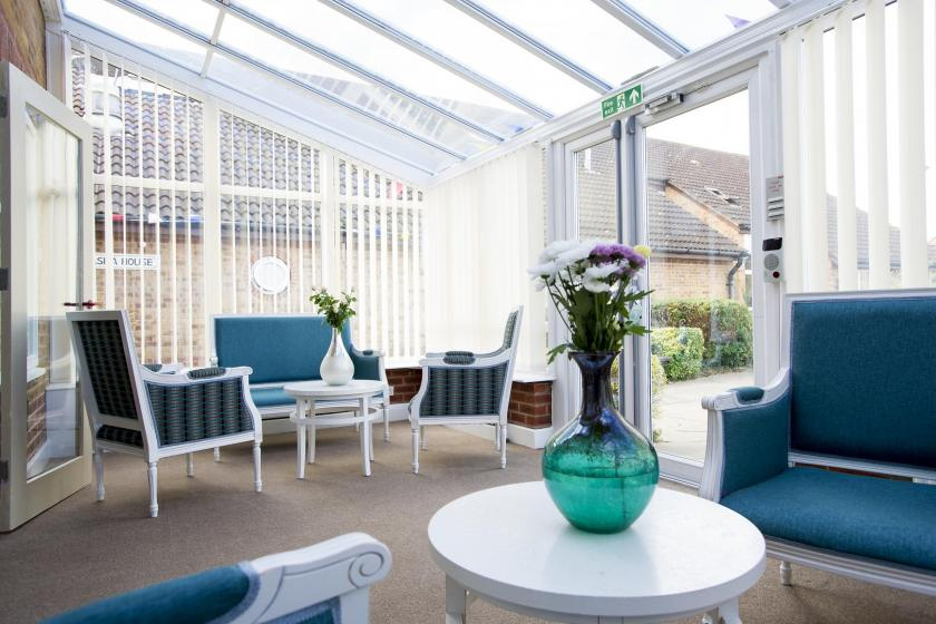 The conservatory provides plentiful seating to admire the gardens at Asra House Residential Care Home