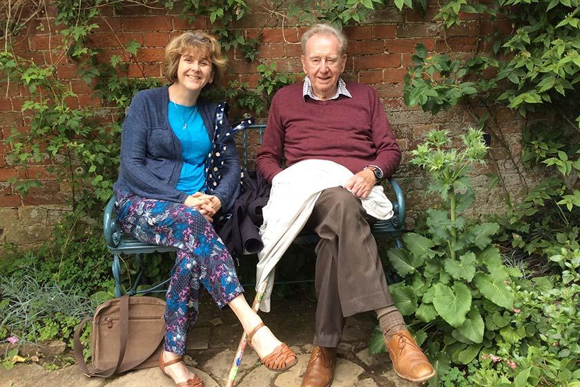Alison Adcock and her late father Michael Atkinson sitting on a garden bench at Heathlands Residential Care Home