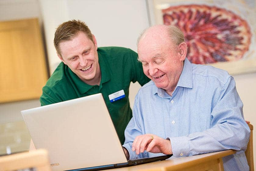 Digital Buddies assist an older man with a computer.