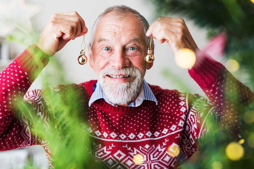 A smiling Sanctuary Care resident celebrating Christmas in a Christmas jumper