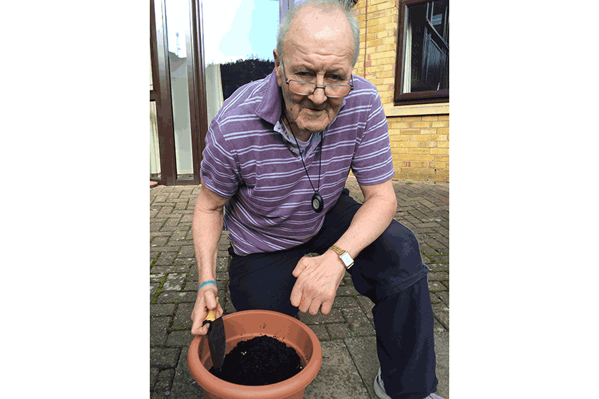 Resident, Geoffrey Leer, gets ready to grow fresh vegetables with the gardening club.