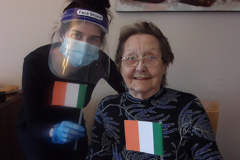 Jessica waves handmade Irish flags with resident, Elsie