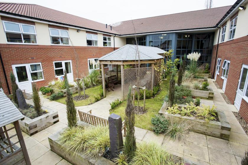 The courtyard garden with raised garden beds at The Beeches Residential Care Home.