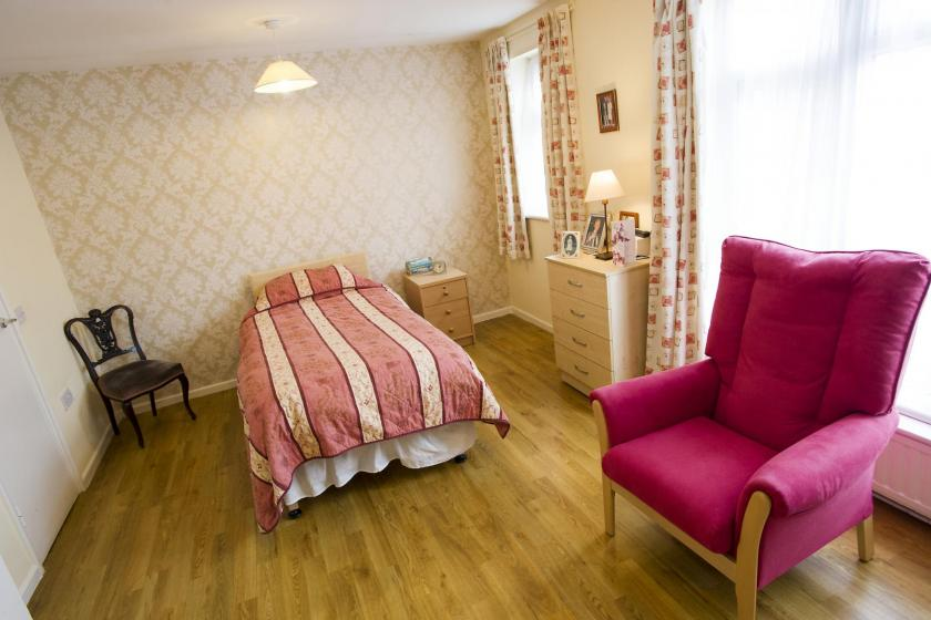 A typical bedroom at the Manse, furnished with residents photo frames and small items that personalise their room.