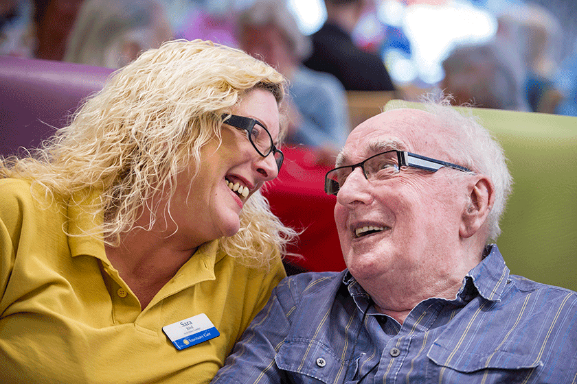A resident smiles with care worker