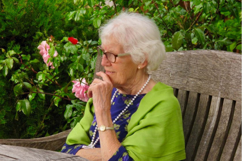 A resident sits in the lovely gardens at Briggs House