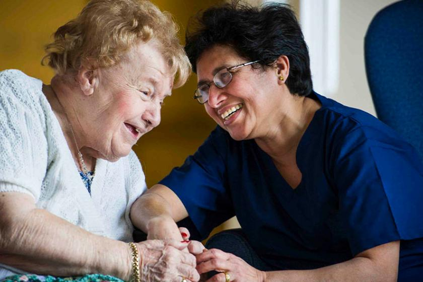 Sanctuary Care staff and resident laughing together