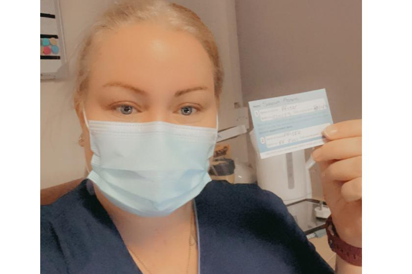 Deputy manager and nurse Sheena Adams wears a mask whilst showing her Covid vaccination card