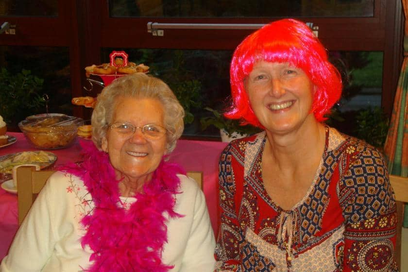 Sanctuary Care staff member and resident in pink fancy dress wig and feather boa.
