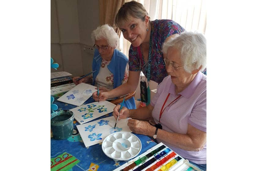 Residents painting flowers.