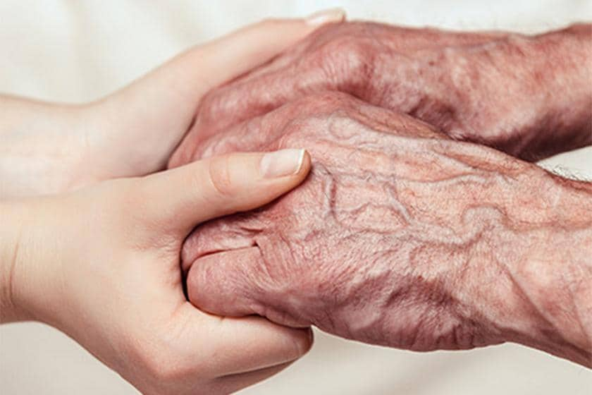 An elderly person and a younger person holding hands.