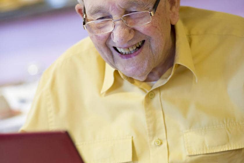 Sanctuary Care resident Harry Dye, catching up with emails on his laptop.