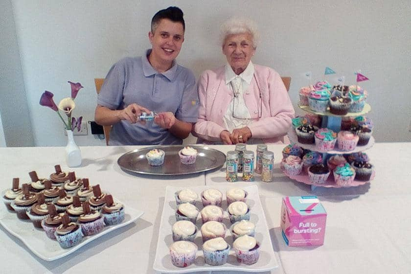 A member of staff and resident show off the display of cakes baked in support of the Alzheimer's Society.