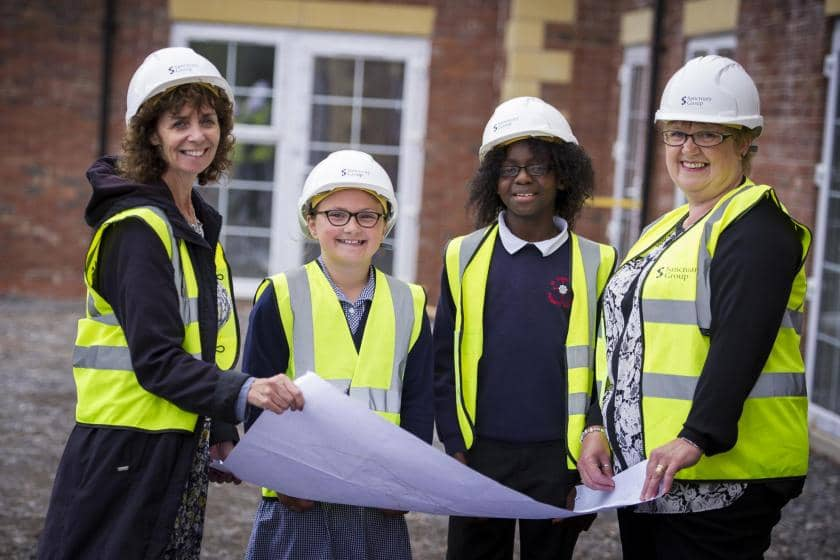 School children wearing hard hats and hi-vis jackets during a visit to a Sanctuary Care development site in Chester.