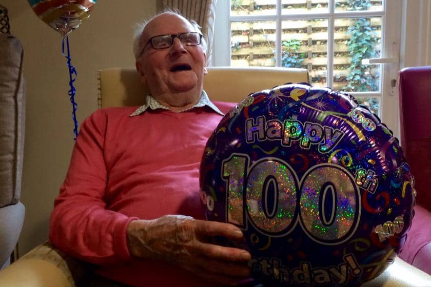 Iffley Residential and Nursing Home resident holds his 'Happy 100th birthday' balloon.