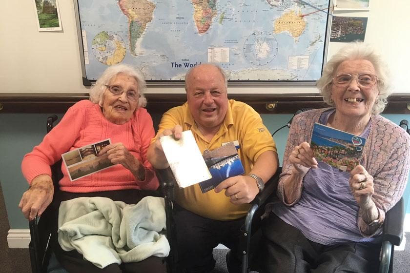 A staff member and residents with their postcards.