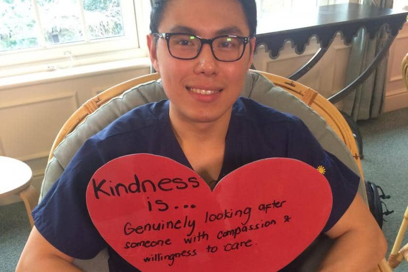 Nurse Louie holds a heart-shaped card which states kindness is genuinely looking after someone with compassion and willingness to care.