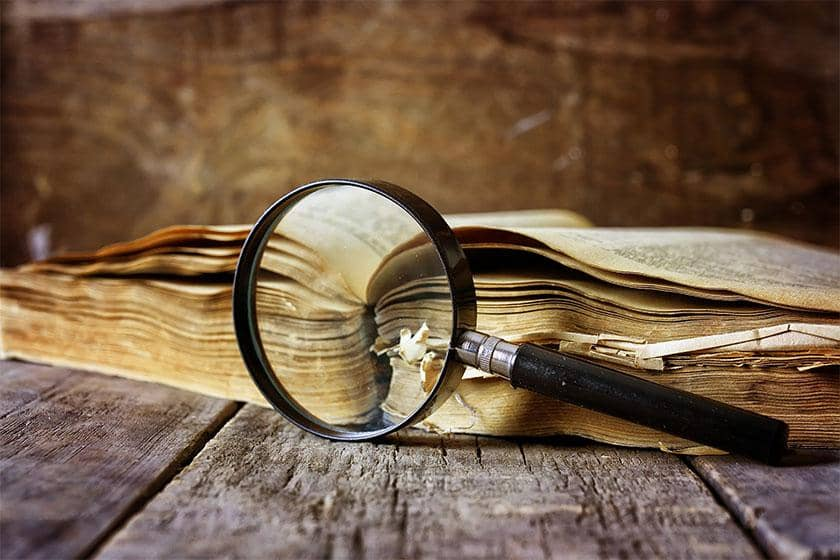 Image showing a magnifying glass next to an old, withered book.