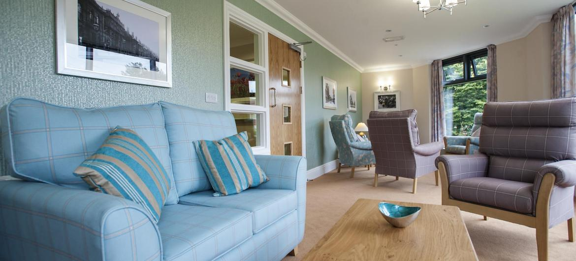 A pretty pastel blue sofa and coordinating chairs in the communal lounge.