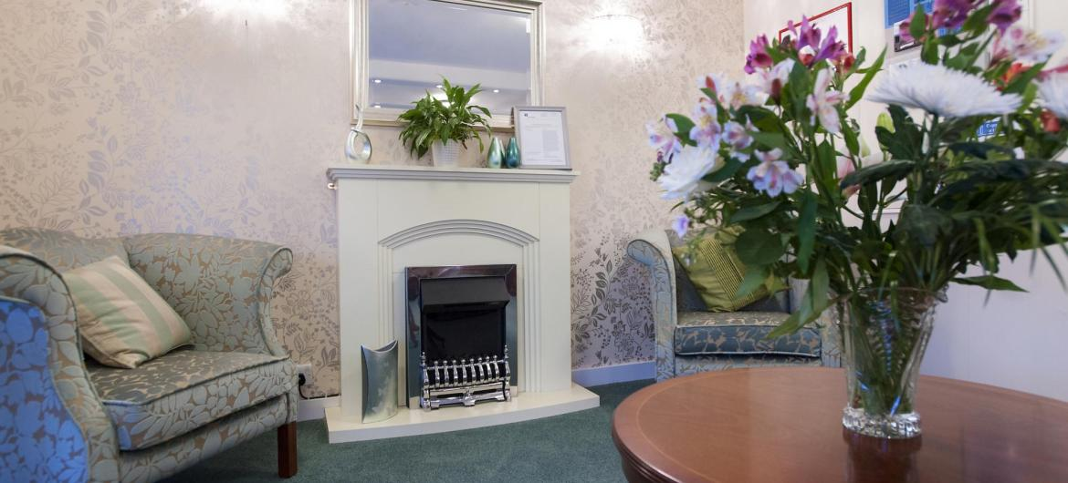 The Regent Residential Care Home reception area with comfy chairs, flowers and an open fire.