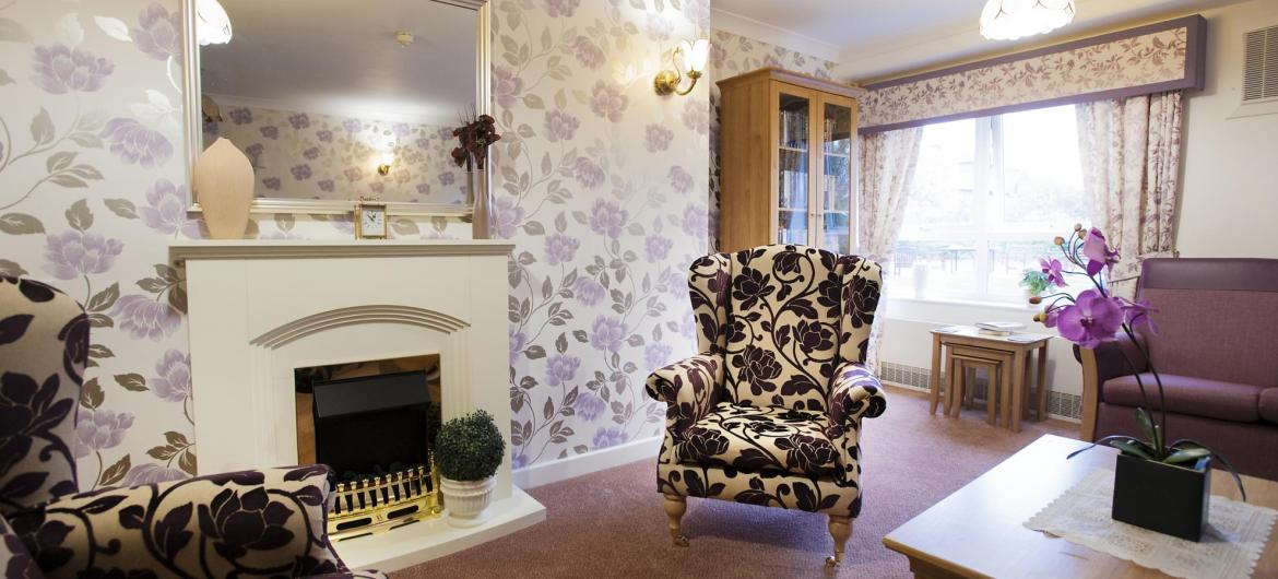 The lounge in the Regent Residential Care Home has comfy chairs and an open fire.
