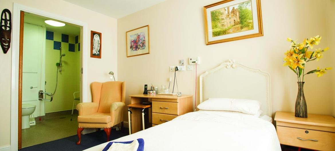 A cosy bedroom with en-suite at the Ravenhurst Residential Care Home.