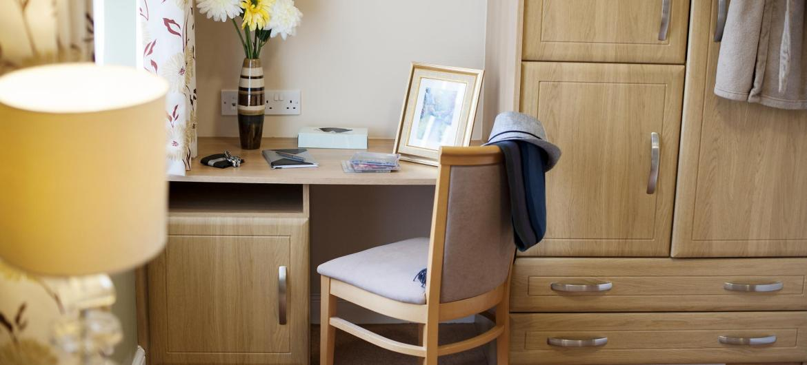A fitted bedroom suite with dressing table, wardrobe and coordinating lamp at The Beeches Residential Care Home.