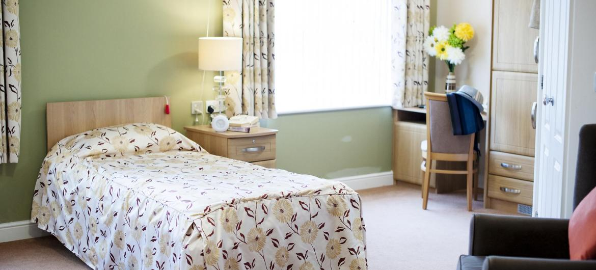 A pretty and airy bedroom at The Beeches Residential Care Home.