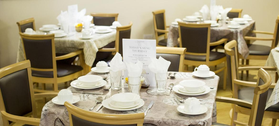 The dining room at Redhill Court Residential Care Home with the tables set with elegant white crockery and napkins.