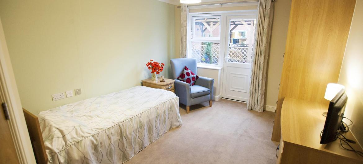 A bedroom at Redhill Court Residential Care Home with a stylish blue chair and comfy cushion.
