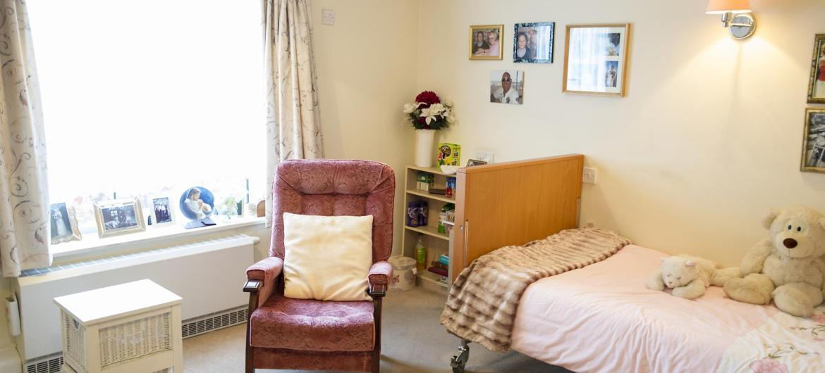 A pretty bedroom with soft toys and comfy chair at Time Court Residential and Nursing Home.