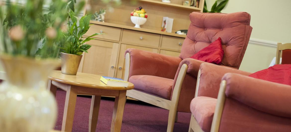 Comfy seats, flowers and a wooden dresser in the lounge at Time Court Residential and Nursing Home.