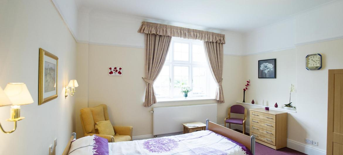 A pretty bedroom at The Winsor Nursing Home with soft lighting and coordinating home furnishings.