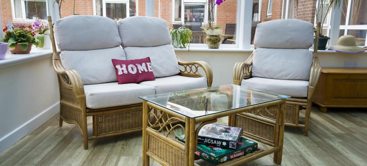 A light and airy conservatory style lounge with wicker chairs and tables at Ivydene Residential and Nursing Home.