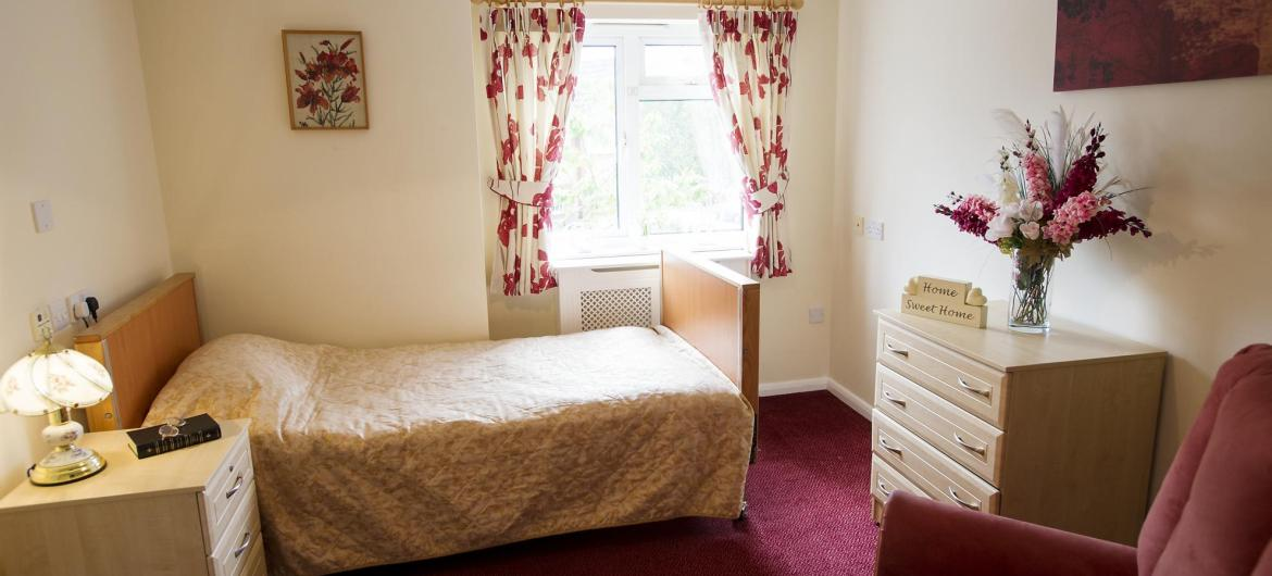 A pretty, traditional bedroom at Ivydene Residential and Nursing Home.